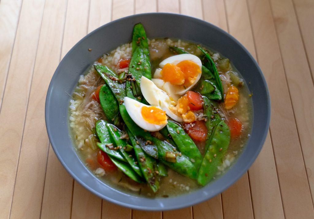 indonesische kippensoep in een kom met ei peultjes en rijst